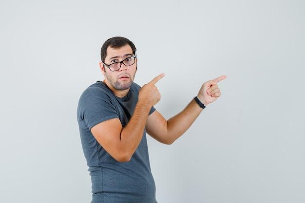 Jonge man wijst opzij in grijs t-shirt en kijkt verward