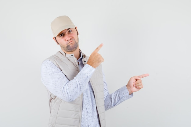 Jonge man wijst opzij in shirt, mouwloos jasje, pet en kijkt ontevreden, vooraanzicht.