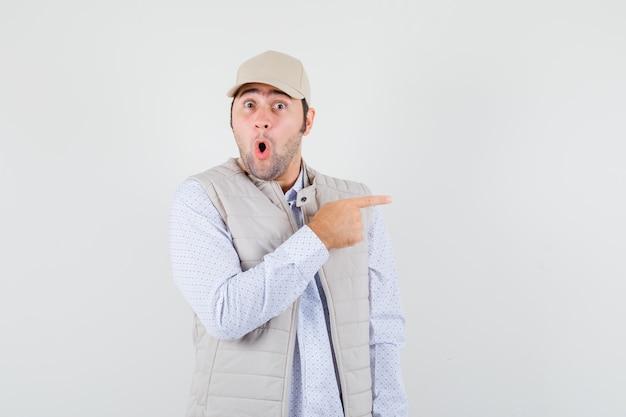 Jonge man wijst opzij in shirt, mouwloos jasje, pet en kijkt verbaasd, vooraanzicht.