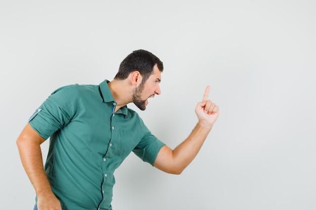 Jonge man wijst opzij terwijl hij op een agressieve manier in een groen shirt schreeuwt en boos kijkt. vooraanzicht.