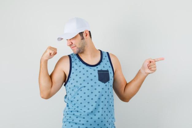 Jonge man wijst opzij, toont winnaargebaar in blauw hemd, pet en kijkt gelukkig.