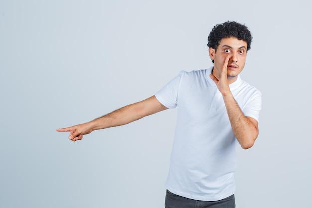 Jonge man wijst opzij, vertelt geheim in wit t-shirt, broek en kijkt nieuwsgierig, vooraanzicht.