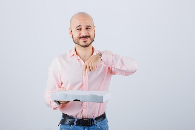 Jonge man wijst pizzadoos in shirt, spijkerbroek en ziet er positief uit. vooraanzicht.