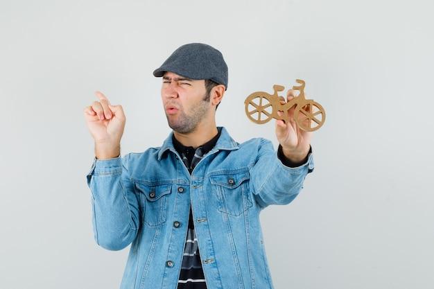 Jonge man wijst terug, houdt houten speelgoedfiets in t-shirt, jas, pet en kijkt ontevreden. vooraanzicht.