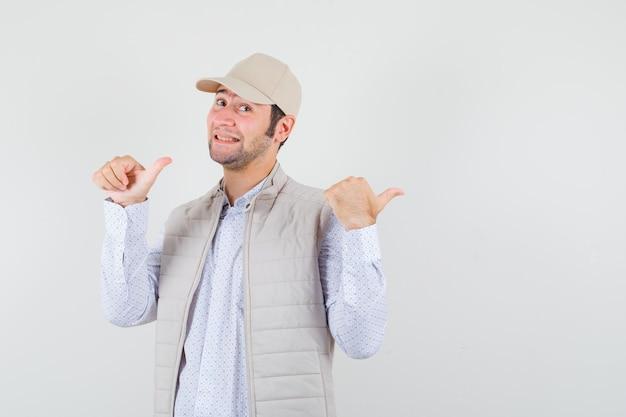 Jonge man wijst terug in shirt, mouwloos jasje, pet en kijkt vrolijk, vooraanzicht.