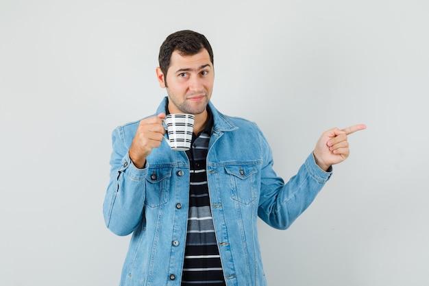 Jonge man wijst weg, houdt kopje drank in t-shirt, jasje en kijkt zelfverzekerd, vooraanzicht.