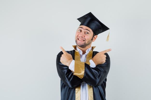 Jonge man wijst weg in afgestudeerde uniform en kijkt optimistisch. vooraanzicht.