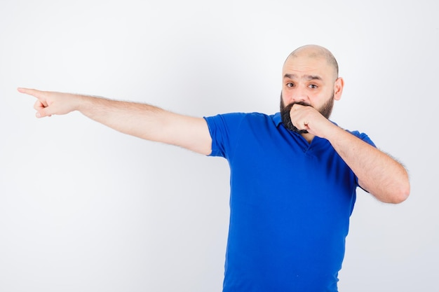Jonge man wijst weg in blauw shirt en kijkt gealarmeerd, vooraanzicht.