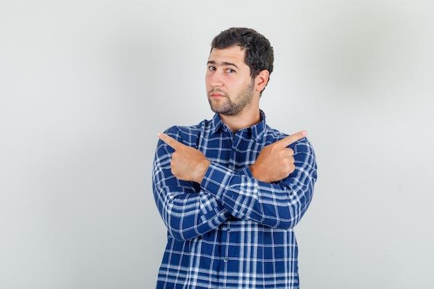 Jonge man wijst weg met gekruiste armen in geruit overhemd en kijkt zelfverzekerd.