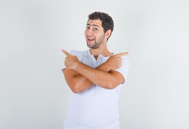 Jonge man wijst weg met gekruiste armen in wit t-shirt en kijkt gelukkig