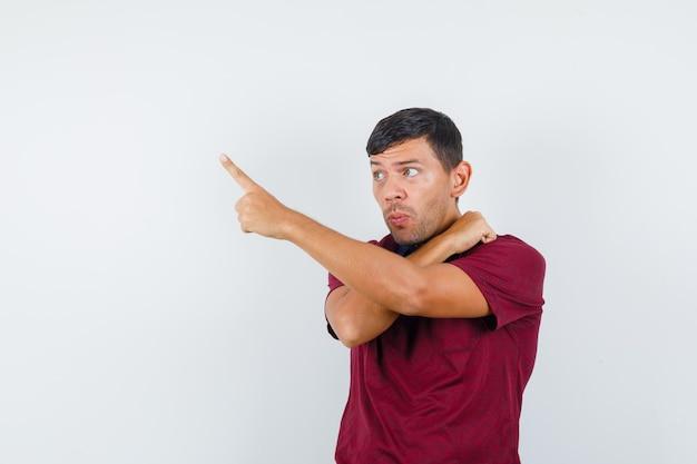 Jonge man wijst weg met vuist op schouder in t-shirt en kijkt nieuwsgierig, vooraanzicht.