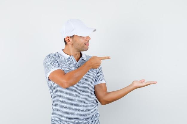 Jonge man wijst weg, spreidt palm opzij in t-shirt en pet en kijkt vrolijk