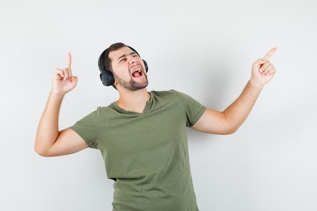 Jonge man wijst weg terwijl hij geniet van muziek in een groen t-shirt en er energiek uitziet