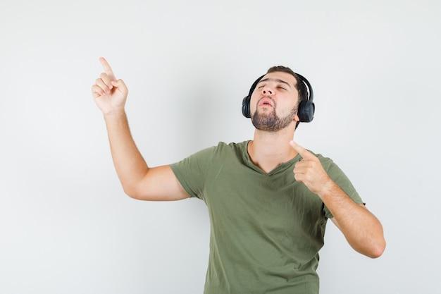 Jonge man wijst weg terwijl hij geniet van muziek in een groen t-shirt en kijkt ontspannen