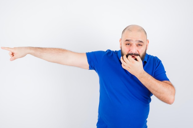 Jonge man wijst weg terwijl hij in blauw shirt fluit, vooraanzicht.