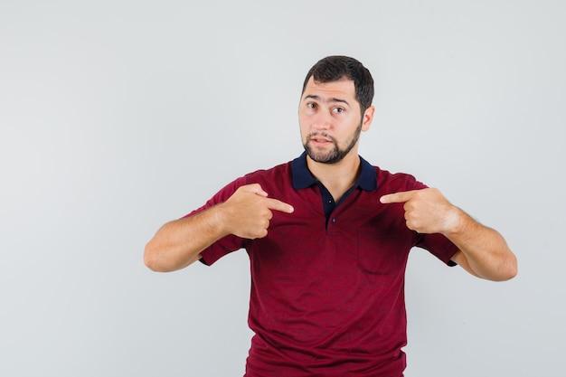 Jonge man wijst zichzelf in rood t-shirt en kijkt voorzichtig. vooraanzicht.