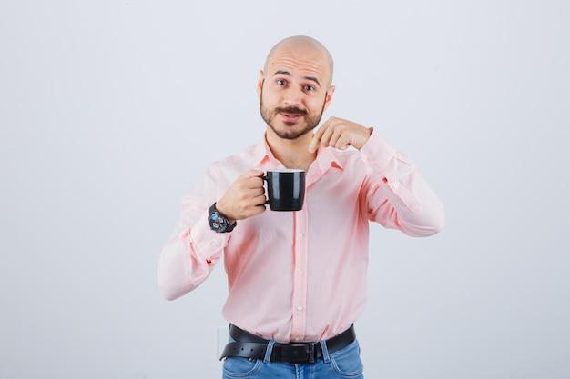 Jonge man wijzend naar beker in roze shirt, spijkerbroek en gealarmeerd, vooraanzicht.
