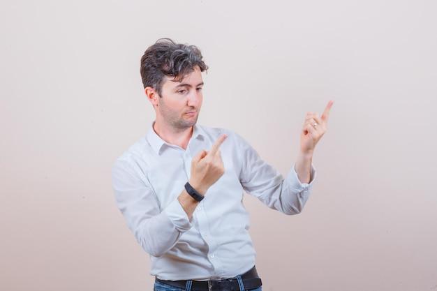 Jonge man wijzend naar de rechterbovenhoek in wit overhemd, spijkerbroek en peinzend kijkend