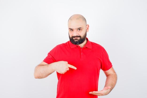 Jonge man wijzend naar zijn linkerhand in rood shirt vooraanzicht.