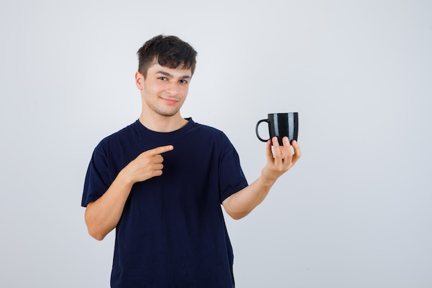 Jonge man wijzend op beker in zwart t-shirt en kijkt zelfverzekerd, vooraanzicht.