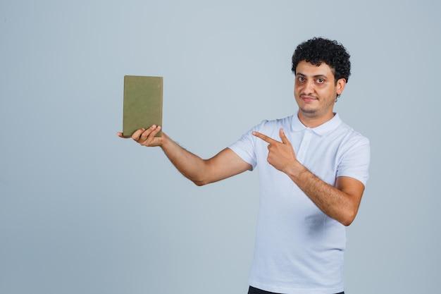 Jonge man wijzend op boek in wit t-shirt en zelfverzekerd kijken. vooraanzicht.