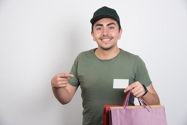 Jonge man wijzend op creditcard tegen witte achtergrond.