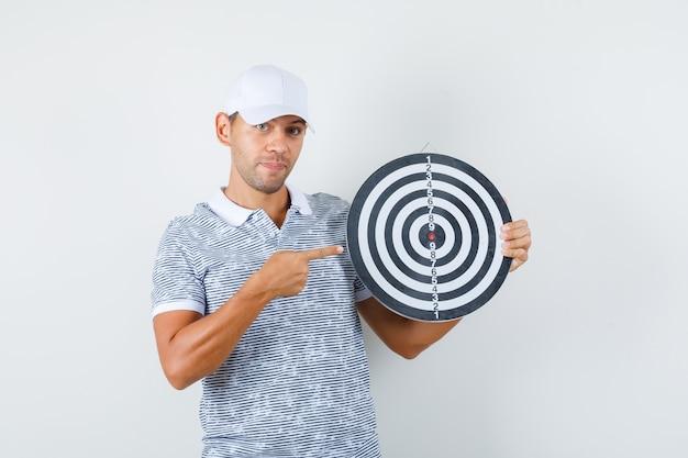 Jonge man wijzend op dartbord in t-shirt en pet en kijkt vrolijk