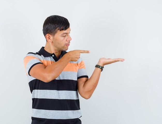 Jonge man wijzend op de handpalm uitgespreid in t-shirt en kijkt gefocust