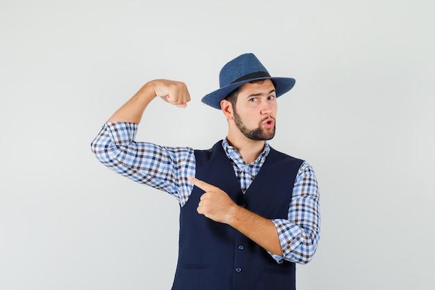 Jonge man wijzend op de spieren van de arm in hemd, vest, hoed en ziet er sterk uit. vooraanzicht.