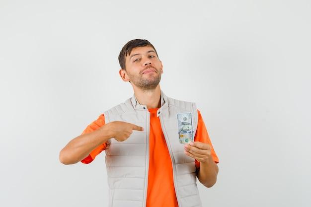 Jonge man wijzend op dollarbiljet in t-shirt, jasje en op zoek zelfverzekerd. vooraanzicht.