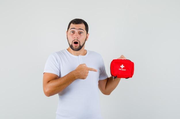 Jonge man wijzend op ehbo-kit in wit t-shirt en kijkt gealarmeerd, vooraanzicht.