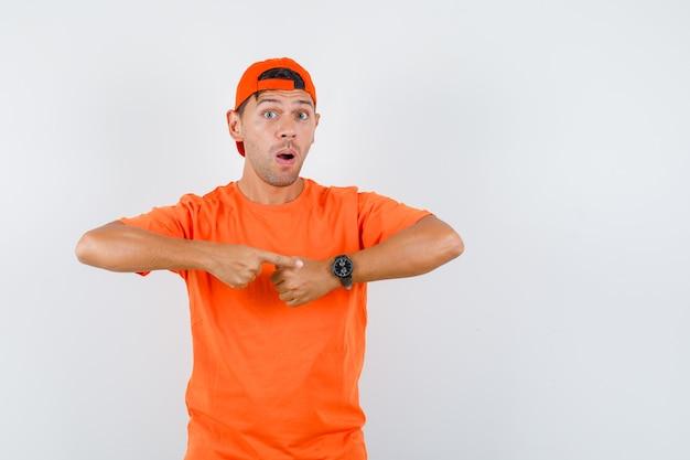 Jonge man wijzend op horloge op pols in oranje t-shirt en pet en kijkt gealarmeerd
