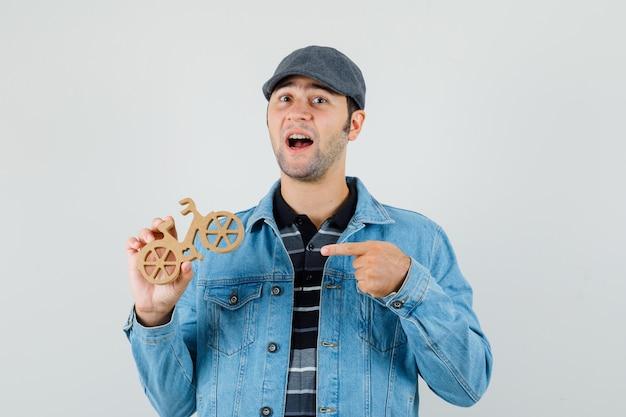 Jonge man wijzend op houten speelgoed fiets in pet, t-shirt, jas en op zoek vrolijk. vooraanzicht.