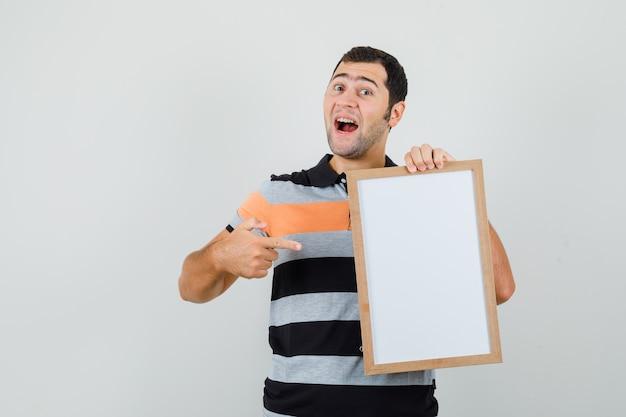 Jonge man wijzend op leeg frame in t-shirt en op zoek spraakzaam.