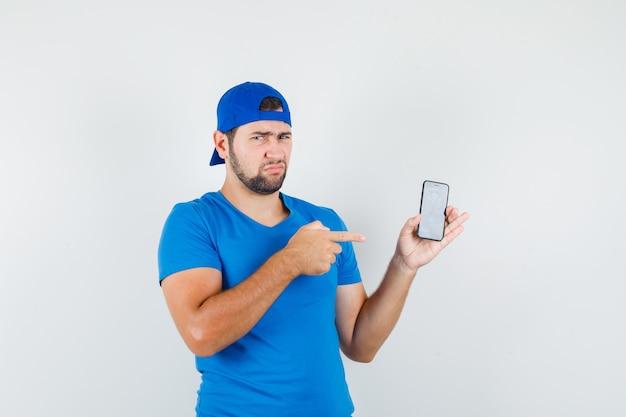 Jonge man wijzend op mobiele telefoon in blauw t-shirt en pet en kijkt ontevreden