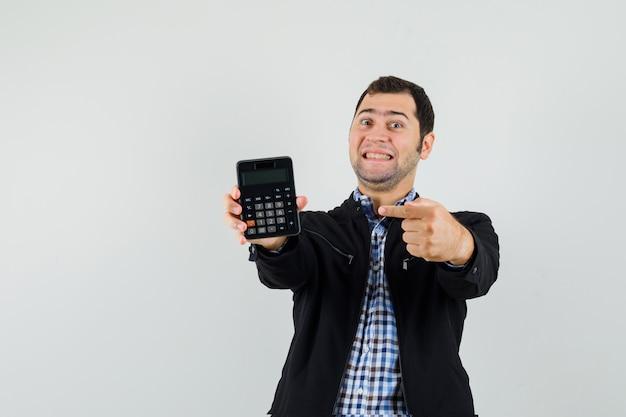 Jonge man wijzend op rekenmachine in overhemd, jasje en op zoek vrolijk