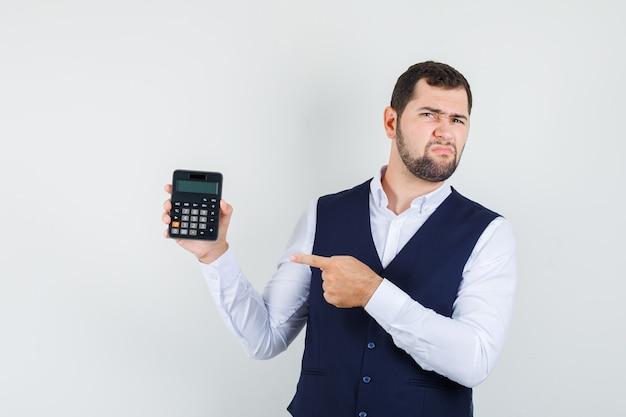 Jonge man wijzend op rekenmachine in overhemd, vest en ontevreden op zoek