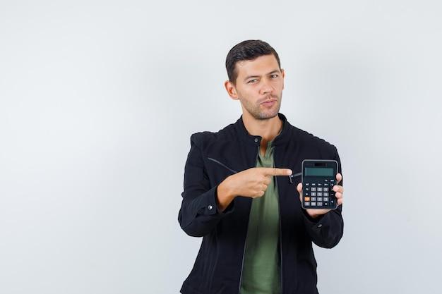 Jonge man wijzend op rekenmachine in t-shirt, jas en er verstandig uitzien, vooraanzicht.