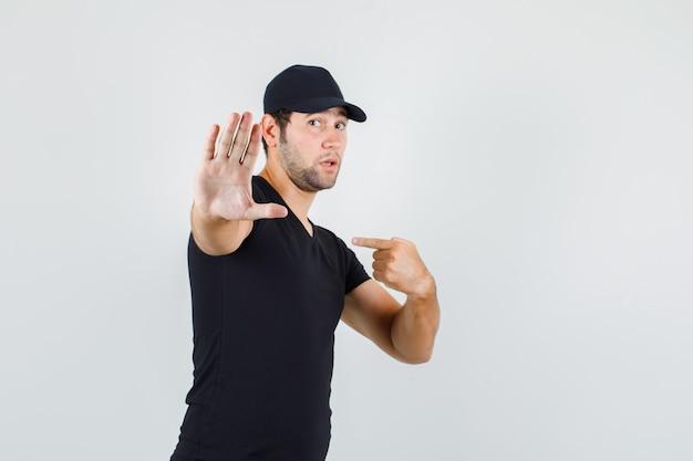 Jonge man wijzend op zichzelf zonder gebaar in zwart t-shirt