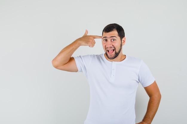 Jonge man wijzend op zijn hersenen in t-shirt en op zoek alwetend. vooraanzicht.