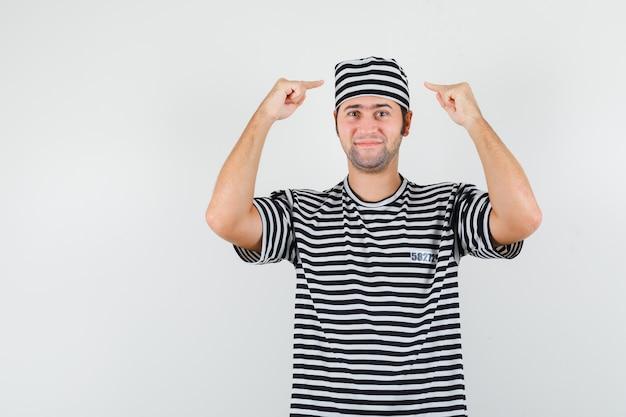 Jonge man wijzend op zijn hoed in t-shirt, hoed en kijkt zelfverzekerd, vooraanzicht.