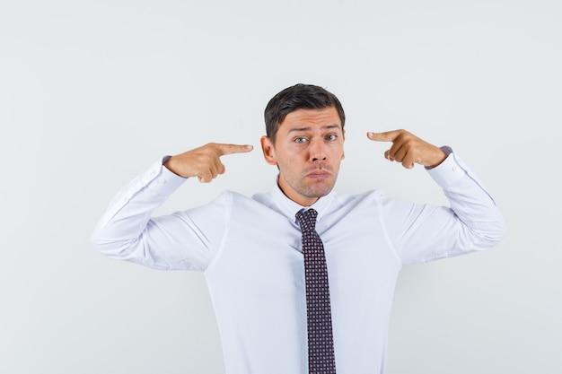 Jonge man wijzend op zijn ogen in wit overhemd, stropdas vooraanzicht.