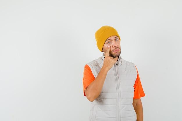 Jonge man wijzend op zijn onderste ooglid in t-shirt, jas, hoed en op zoek verdrietig. vooraanzicht.