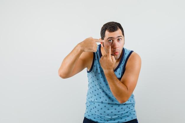Jonge man wijzend op zijn ooglid getrokken door vinger in blauw hemd