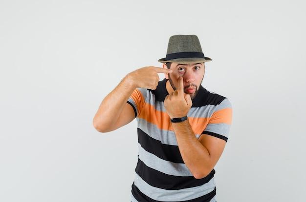 Jonge man wijzend op zijn ooglid getrokken door vinger in t-shirt, hoed, vooraanzicht.