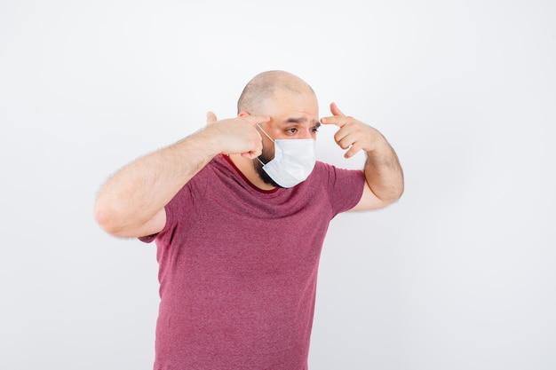 Jonge man wijzend op zijn slapen in roze t-shirt, masker vooraanzicht.