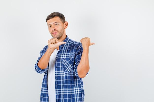 Jonge man wijzende duimen naar de andere kant en lachend in shirt, vooraanzicht.