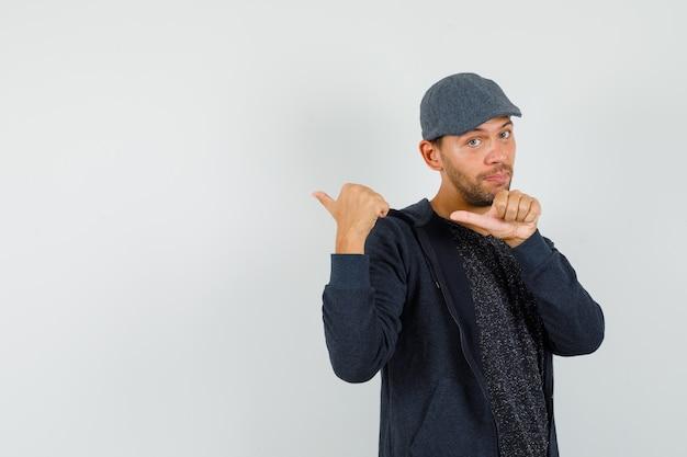 Jonge man wijzende duimen weg in t-shirt, jasje, pet en op zoek zelfverzekerd