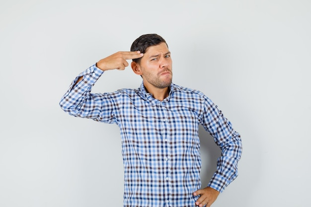Jonge man wijzende hand en vingers naar het hoofd als pistool in geruit overhemd en op zoek verdrietig.