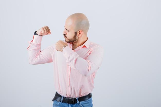 Jonge man wijzende spieren van de arm in shirt, spijkerbroek en trots op zoek, vooraanzicht.
